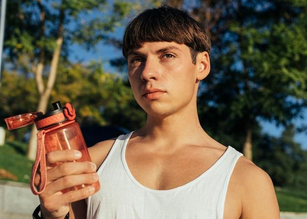 Man met fles water te drinken na het trainen