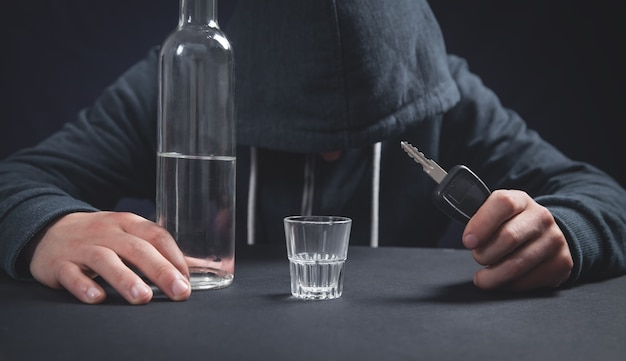 Man met fles wodka en autosleutel. rijden onder invloed
