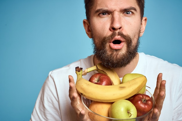 Man met fruit in een wit t-shirt op een blauw