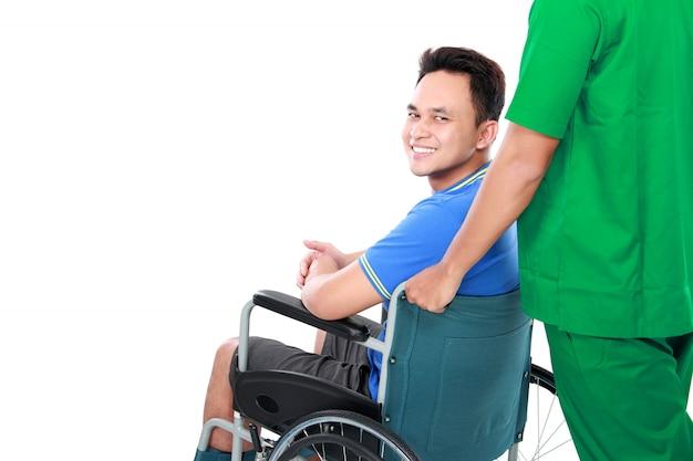 Man met gebroken arm en voet met rolstoel