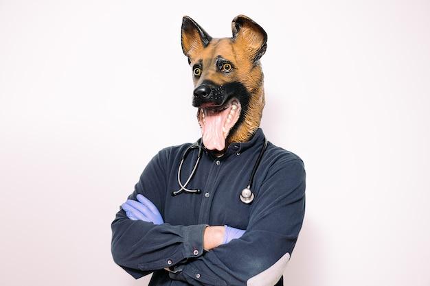 Man met gekruiste armen en hondenmasker en stethoscoop