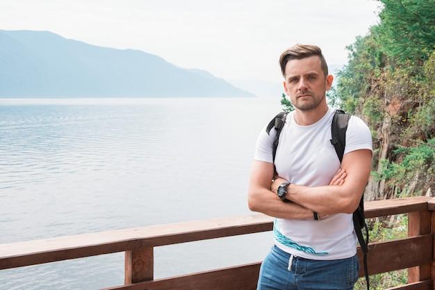 Man met gekruiste armen en rugzak aan het meer