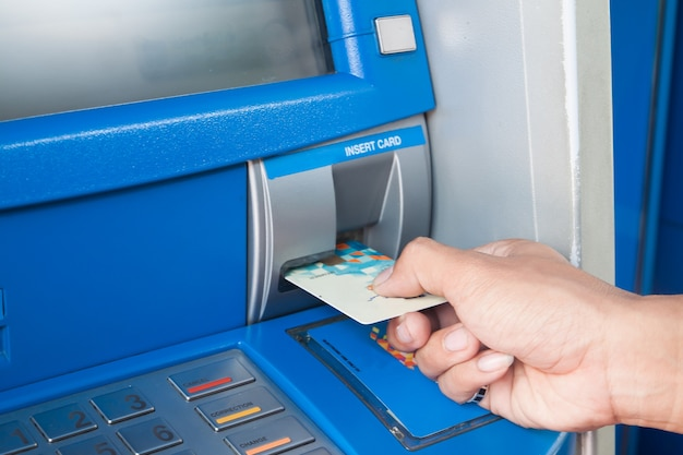 Man met geldautomaat met zijn creditcard