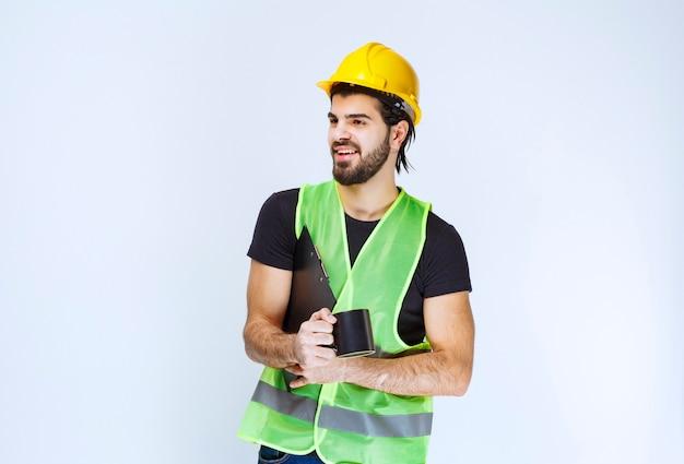 Man met gele helm met projectmap en een kopje koffie.
