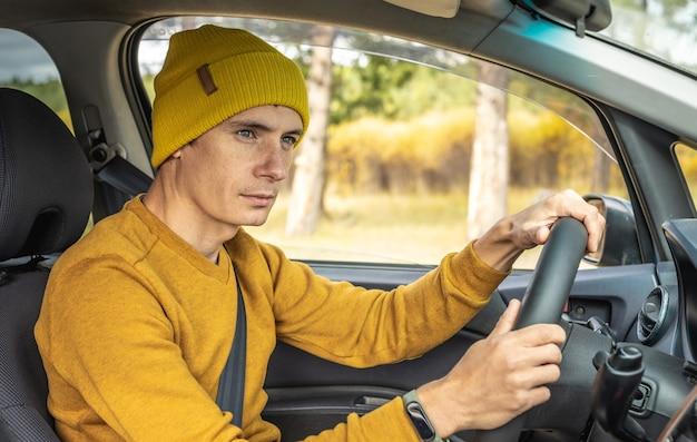 Man met gele hoed en trui rijdt in een auto langs de herfstbosweg. concept van natuur, reizen en herfststemming.