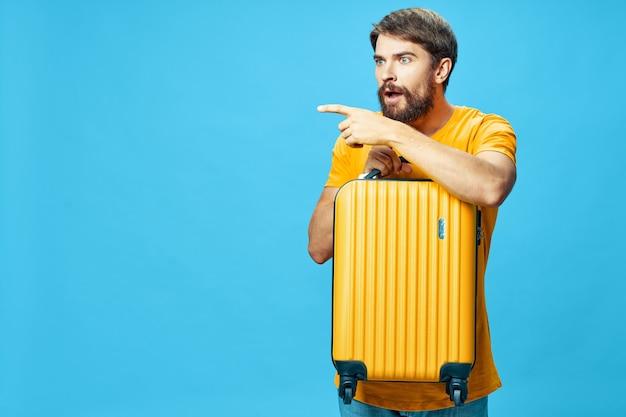 Man met gele koffer op blauwe achtergrond bijgesneden weergave