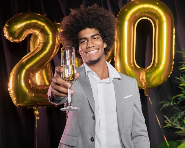Man met gelukkig nieuwjaar 2020 ballonnen en glas champagne