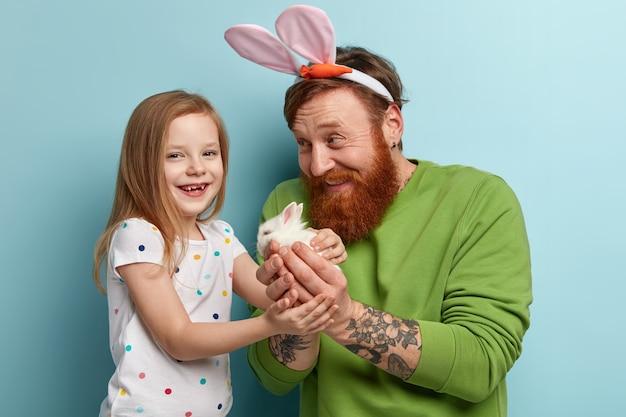 Man met gember baard dragen kleurrijke kleding en zijn dochter met konijn