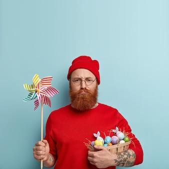 Man met gemberbaard die kleurrijke kleding draagt en paaseieren houdt