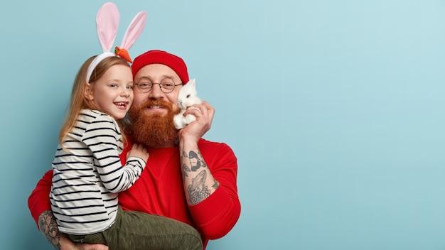 Man met gemberbaard die kleurrijke kleding draagt en zijn dochter vasthoudt