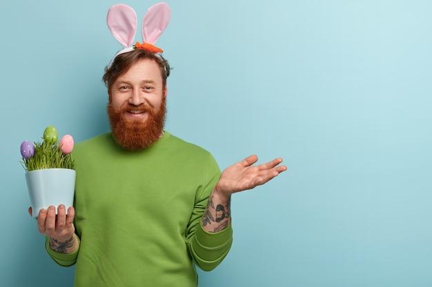 Man met gemberbaard die kleurrijke kleding en konijnenoren draagt