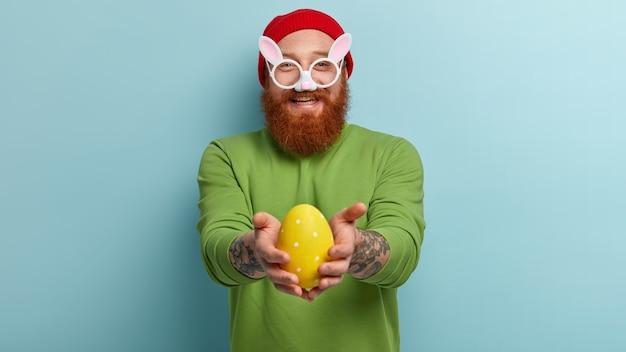 Man met gemberbaard die kleurrijke kleding en konijntjesglazen draagt