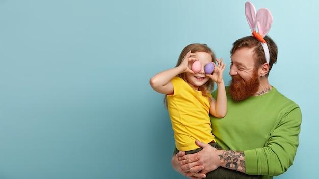 Man met gemberbaard die kleurrijke kleding en konijntjesoren draagt die zijn dochter vasthouden