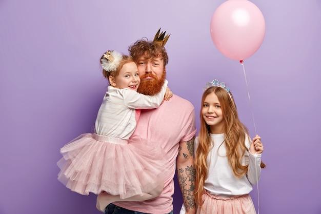 Man met gemberbaard en zijn dochters met feestaccessoires