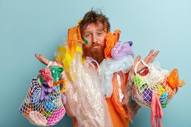 Man met gemberbaard met zakken met plastic afval