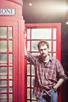 Man met geruit overhemd en spijkerbroek bij de rode telefooncel