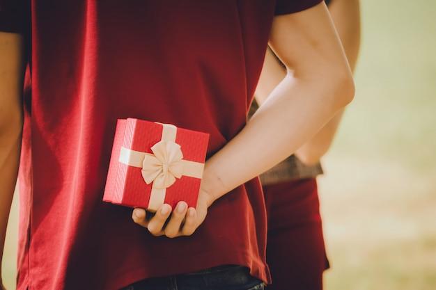 Man met geschenkdoos achter zijn rug