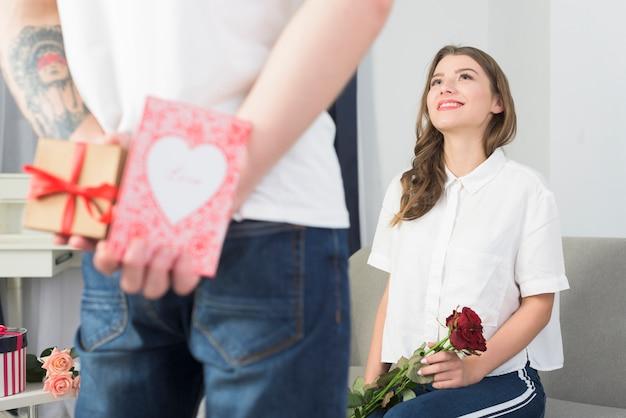 Man met geschenkdozen voor vrouw achter rug