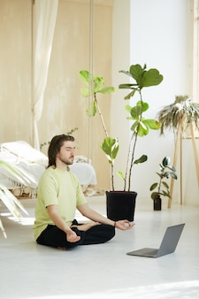 Man met gesloten ogen en armen in yoga mudra mediteren, knappe yogaleraar maken online les van concentratie oefenen met laptop