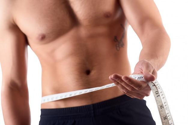 Man met gespierd lichaam zijn buikspieren meten