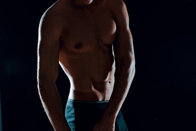 Man met gespierde buikspieren bijgesneden weergave van sportschool donkere achtergrond