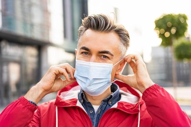 Man met gezichtsmasker en sociaal afstandsconcept