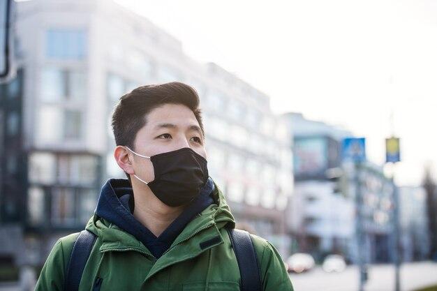 Man met gezichtsmasker in de stad, coronaviruspreventie en beschermingsconcept. ruimte kopiëren.