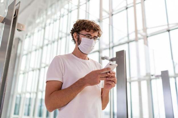 Man met gezichtsmasker in luchthaven en met behulp van smartphone