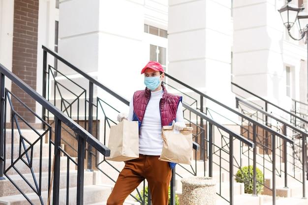 Man met gezichtsmasker levert eten en boodschappen tijdens virusepidemie.