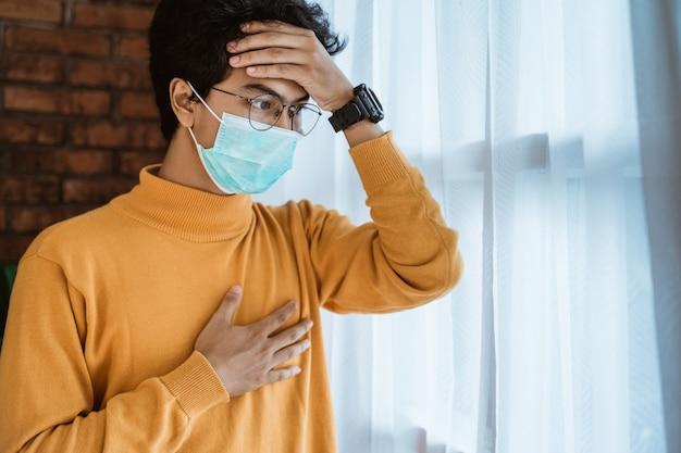 Man met gezichtsmaskers kijkt uit het raam