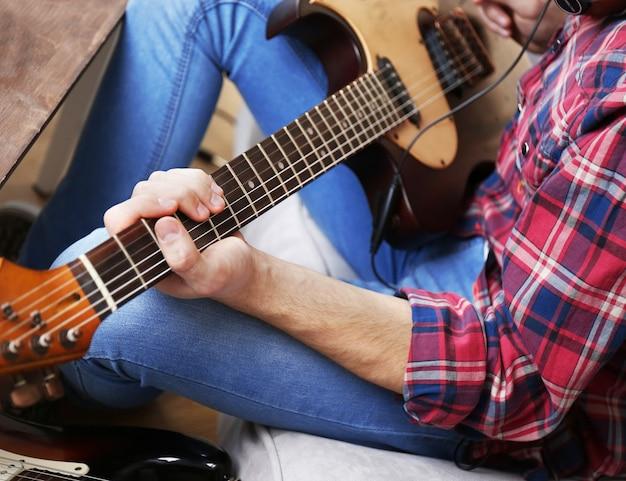 Man met gitaar binnenshuis