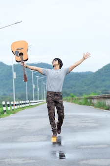 Man met gitaar staande op de dam, vrachtbroek