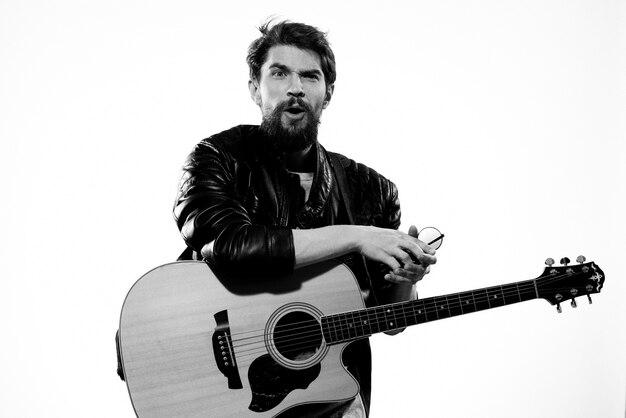 Man met gitaarmuziek in zwart lederen jas geïsoleerd