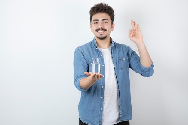 Man met glas water en ok teken geven.