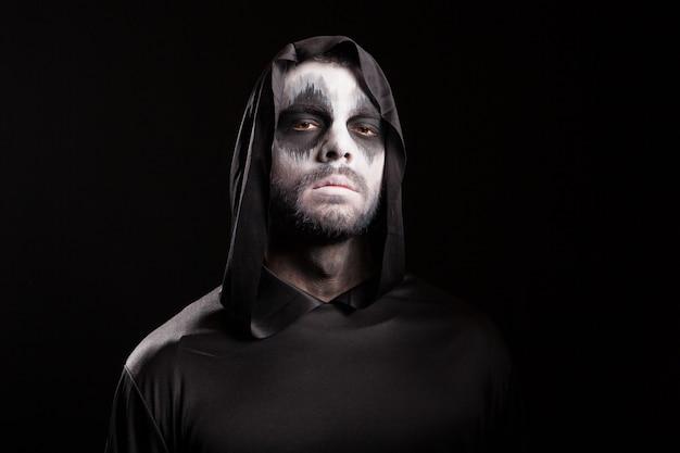 Man met griezelig gezicht verkleed als magere hein op zwarte achtergrond.