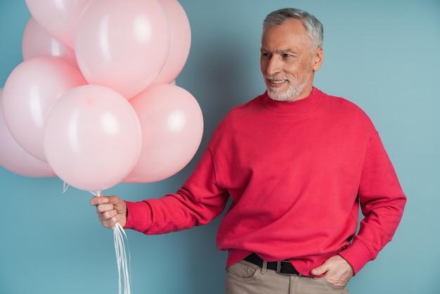 Man met grijs haar en baard houdt roze ballonnen vast. glimlachende man poseren, wegkijken