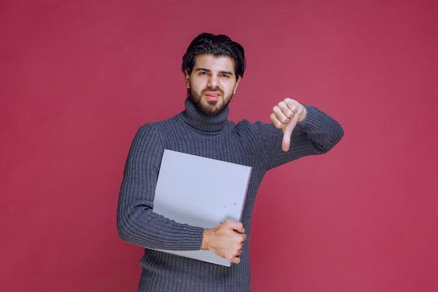 Man met grijze map maakt duim omlaag omdat hij het project niet leuk vond.