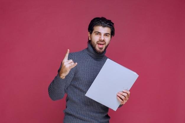Man met grijze map maakt zijn wijsvinger omhoog.