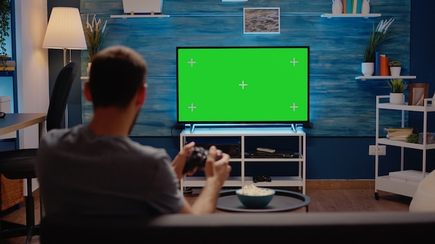 Man met groen scherm moderne tv in woonkamer
