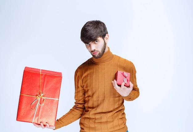Man met grote en kleine rode geschenkdozen in beide handen.