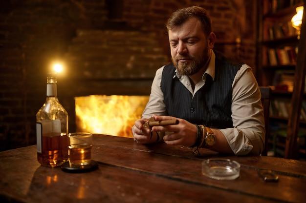 Man met guillotine snijdt een sigaar, houten tafel. tabaksrookcultuur. mannelijke roker vrije tijd met glas alcohol