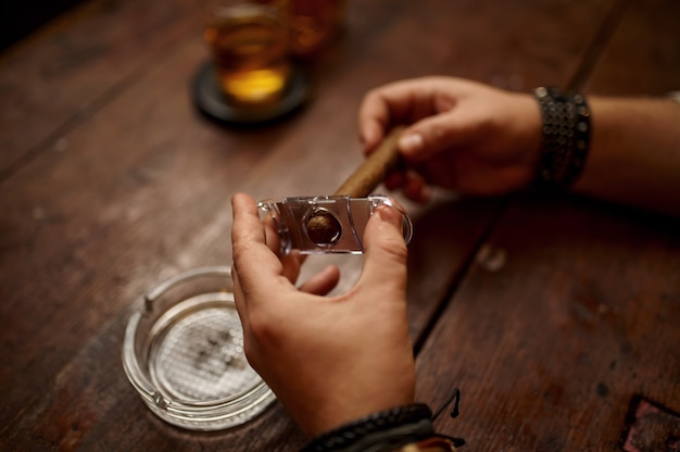 Man met guillotine snijdt een sigaar, houten tafel. tabaksrookcultuur, specifieke smaak. mannelijke roker vrije tijd met glas alcohol
