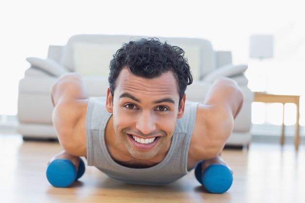 Man met halters doen push-ups in de woonkamer
