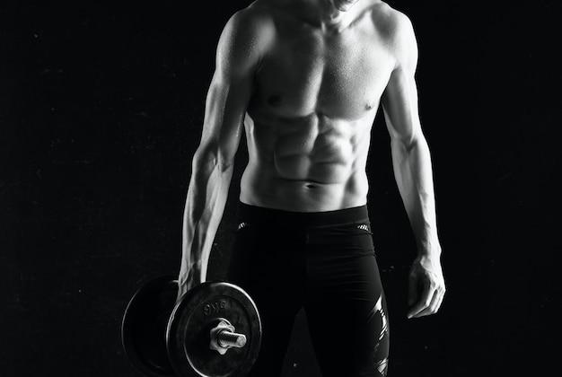 Man met halters in zijn handen naakt gespierd lichaam training donkere achtergrond