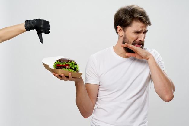 Man met hamburger in witte t-shirt walging dieet calorie