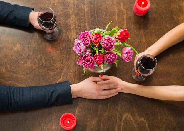 Man met handen met vrouw aan tafel met glazen en bloemen