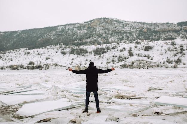 Man met handen omhoog op de oever van de rivier bedekt met ijsschotsen kijken naar het noordse landschap