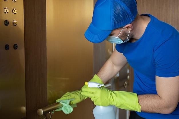 Man met handschoenen en een masker veegt de knoppen en de leuning van het schoonmaakpersoneel van de lift af en desinfecteert de lift om besmetting te voorkomen