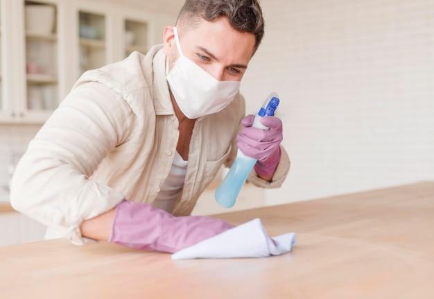 Man met handschoenen met ontsmettingsmiddel