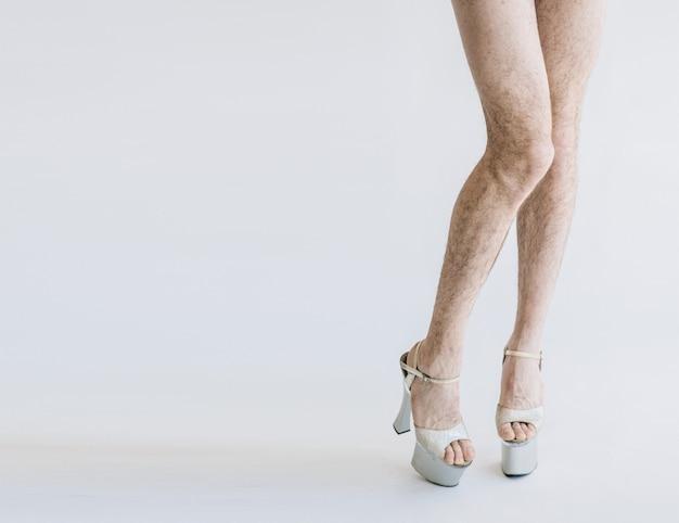 Man met harige benen en hoge hakken geïsoleerd, kopieer ruimte